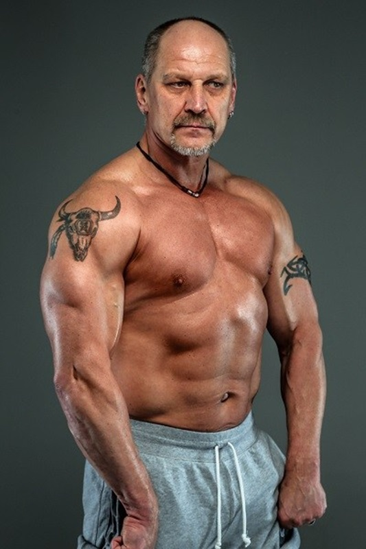 Aged man showing muscles. Studio shoot. Isolated on dark grey